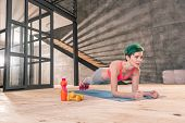 Woman Feeling Energized While Finishing Her Workout With Plank poster