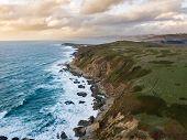 Aerial view of waves crashing along the rocky California coast near San Francisco. poster