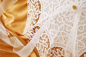 Beautiful lace parasol with chiffon ribbon on gold satin background with copy space.  Macro with shallow dof.