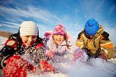 Joyful kids in winterwear having happy time outside