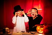 stock photo of antichrist  - Photo of two eerie boys frightening people on Halloween - JPG