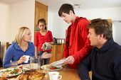 Unhelpful Teenage Clearing Up After Family Meal In Kitchen
