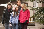 Teenage Family Walking Along Snowy Town Street In Ski Resort