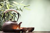 Teapot and cups on table with bamboo leaves.