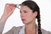 Perplexed woman taking her glasses off to get a better look at something