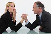 Blond woman arm wrestling her boss