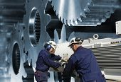 stee-workers, engineers operating a giant gear machinery, gear wheels in blue toning concept