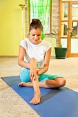 Happy young woman doing leg self massage at home. Healthy life.