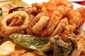 closeup of a spanish combo platter with fries, grilled pepper and fried shrimps and calamares