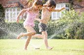 picture of sprinkler  - Two Children Running Through Garden Sprinkler - JPG