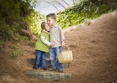 Adorable Brother and Sister Children with Basket Hugging Outside.