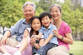 Chinese Grandparents Sitting With Grandchildren In Park