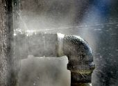 stock photo of leaked  - Old rusty pipe with leak and water spraying out - JPG