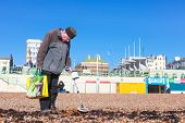 BRIGHTON, UK - FEBRUARY 8, 2011: Pensioner looking for metal objects on beach with metal detector on February 8, 2011 in Brighton, UK. An estimated 2 million pensioners living below the breadline.