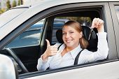 prosperous young woman holding car key and showing thumbs up