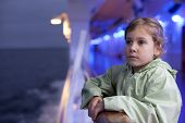 little girl holding on handrails on large passenger ship at night