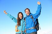 Happy hiking couple cheering in winning success concept. Young woman and man hiker holding around eachother elated and cheerful with arms raised in the sky. Asian girl and Caucasian male hikers.
