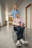 Nurse puching wheelchair of patient with arm sling in hospital corridor