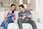 stock photo of fellowship  - Two people sitting on the couch in the living room while using a tablet computer - JPG