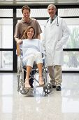 Pregnant woman in wheelchair, partner and doctor smiling in hospital corridor