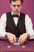 Dealer shuffling the deck of cards at poker table