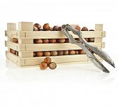 hazelnut filbert on wooden crate with Nutcracker isolated on white background
