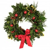 Christmas decorative wreath of holly, ivy, cedar cypress leaf sprigs and red bauble decorations with