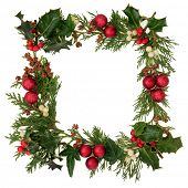 Christmas decorative border of holly, ivy, mistletoe, cedar leaf sprigs with pine cones and red baub