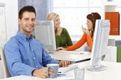 Casual happy businessman with sitting at desk in office, smiling at camera, with colleagues in background.