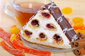 piece of a pie with cherries, tea and candied fruits