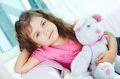 Porträt von schönen Mädchen mit Teddybär sitzend auf Sofa und Booking in die Kamera