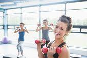Sonriendo pesos elevación de mujer mientras que las mujeres haciendo ejercicios aeróbicos en el gimnasio