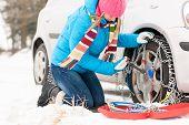 Cadeias de mulher colocando pneus de carro de neve inverno quebrado de fixação