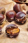 some roasted chestnuts on a background with autumn leaves