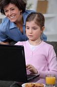 Little girl using laptop at home