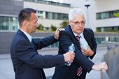 Business man helping senior with heart attack with a bottle of water