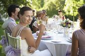 stock photo of flute  - Portrait of beautiful bride holding champagne flute while sitting with guests at wedding table - JPG