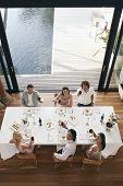 Retrato de alto ángulo de amigos multiétnicas tostado vino en la cena