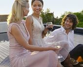 Tres jóvenes amigos bebiendo y socializar en el porche