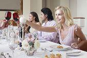 Hermosa joven brindando vino tinto con amigos en la mesa de la cena