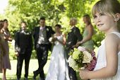 Cute little bridesmaid holding bouquet in lawn with guests and wedding couple in background
