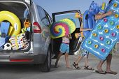 Father and two children unloading beach accessories from car