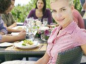 Retrato de mujer joven hermosa con amigos teniendo comida al aire libre