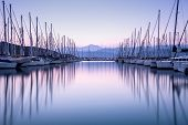 Large yacht harbor in purple sunset light, luxury summer cruise, sailboats in sunrise, leisure time,