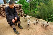 Guizhou Province, China - Older Chinese Lady In Green Running Shoes, Sitting Outside His Home