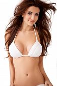 Charming sexy young brunette woman with large breasts and windblown hair posing in a white bikini  upper body isolated studio portrait