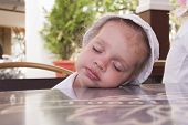 Two-year-old girl asleep at a table in the street cafe