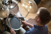 stock photo of drum-kit  - The drummer with headphones plays the drum kit in the studio - JPG