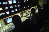 foto of programmers  - Rear view of operators in central control room at television station - JPG