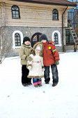Three Kids Play Outside Of House In Winter